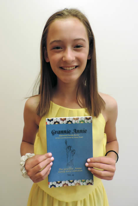 "Grannie Annie published student 2019, holding a copy of ""Grannie Annie, Vol. 14"""