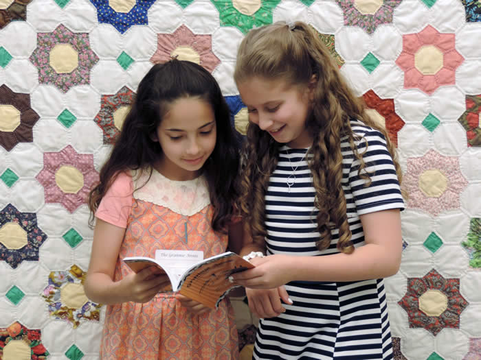 "Two Grannie Annie published students 2018, looking at a copy of ""Grannie Annie, Vol. 13"""